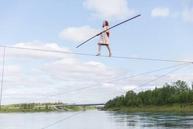 Virš plačios ir sraunios Ounasjoki'o upės - lyno akrobatė Sanja Kosonen. Ben Hopper nuotrauka iš fmq.fi